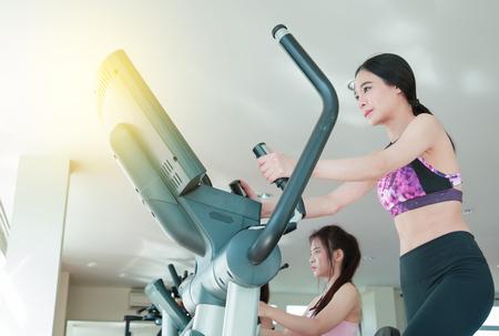 Happy cheerful athletes training on exercise bike. Stock Photo