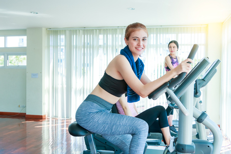 Happy cheerful athletes training on exercise bike. Foto de archivo