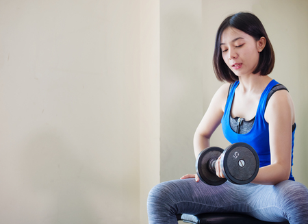 Young Asian woman training weight lifting at gym,  Archivio Fotografico