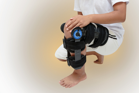 Woman's leg in knee brace for stabilization and support with path Stock Photo