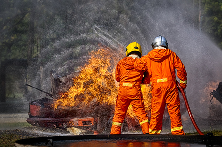Firefighters spraying high pressure water to fire, firefighting training Stok Fotoğraf