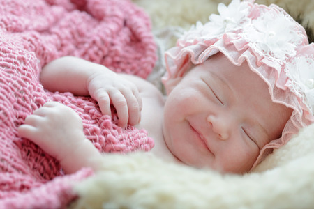 Newborn baby girl smiling in a dream ,Newborn baby girl is sleeping on fur blanket