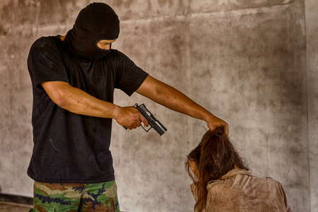 A terrorist man in mask holding gun kidnapping young women for a hostage in abandoned building.  Stok Fotoğraf