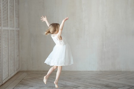Ein kleines Mädchen tanzt in einem Zimmer in einem schönen Kleid Standard-Bild