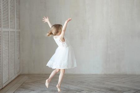 A little girl dancing in a room in a beautiful dress Standard-Bild