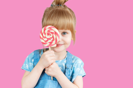 sympathetic: Isolated on bright background, studio. Beautiful little girl with lollipop