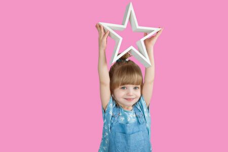 Little girl is smiling on the background in the studio with a star in hands