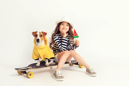 Girl is siting with her dog on skateboard