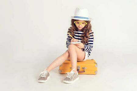 Girl is is sitting on a suitcase and writing