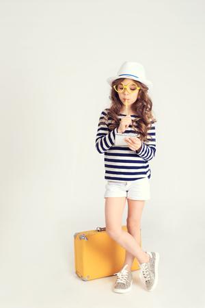 snění: Thinking girl with notebook and suitcase Reklamní fotografie
