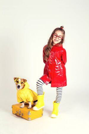 Girl and her pet are wearing glasses and raincoats