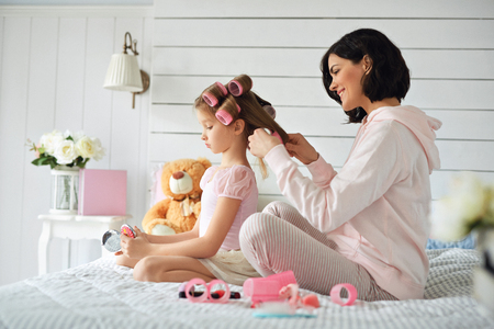 Mother is making hairstyle her daughter Stock Photo