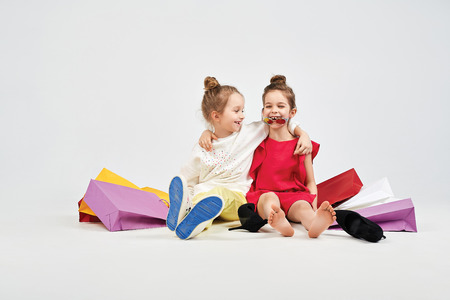 Laughing girls are sitting with shoppers bags