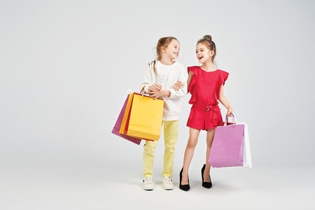 Laughing girls with shoppers bags