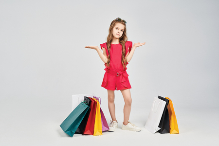 Little girl is standing around shoppers bags