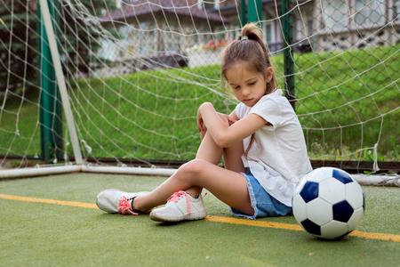 작은 아이 스포츠 옷을 입고 축구 게이트 근처 잔디밭에 앉아 큰 축구 공을 찾고, 그녀의 게임을 잃어버린 후 나쁜 분위기. 스포츠 소녀 그녀의 동시대