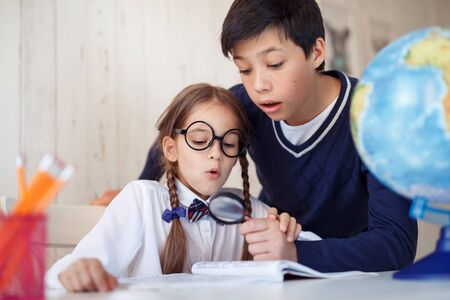 see through: Two pupils staring through lens in book being surprised to see such big size of letters. Schoolgirl with pigtails, wearing big glasses and shirt having fun with her male friend while using magnifier Stock Photo