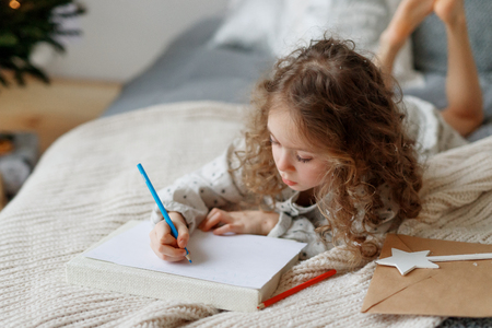 Portait of small lovely beautiful curly child draws pictures on blank white sheet of paper, wants to congratulate her best friend with coming New Year, lies on comfortable bed. Talented female kid.