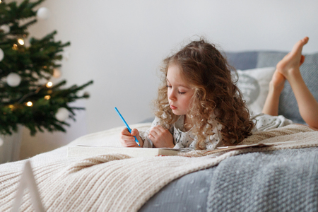 Indoor shot of attentive pretty small girl writes letter to Santa Claus before Christmas, thinks what present she expects, wants all dreams and wishes come true, lies on comfortable bed indoor.