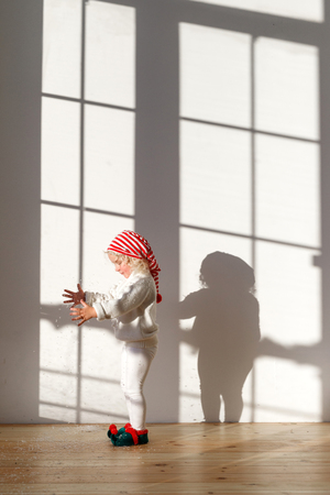 Small adorable blonde pretty female girl stands in spacious room, wears white costume, red hat and elf s shoes plays with something, being along, anticipates coming holidays. Childhood concept.
