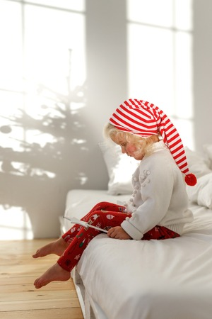 Little blonde child in Christmas hat sits on bed with white bedclothes, plays with magic wand, has serious concentrated expression, thinks about something majestic or miracle. Childhood concept Stock Photo