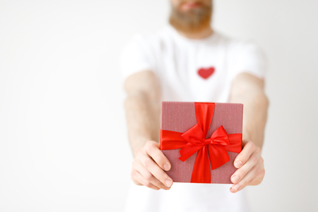 Cropped image of unrecognizable bearded male holds wrapped present box with red ribbon, isolated over white studio background, going to present it to girlfriend. Gift for you. Holiday concept
