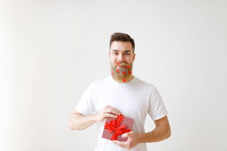 Cheerful bearded male holds wrapped gift box, dressed in casual white t shirt, has beard decorated with paper red hearts, glad to recieve present, celebrates his birthday together with friends