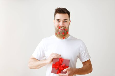 Horizontal shot of cheerful bearded male with trendy hairdo, holds gift box, prepares surprise for girlfriend or friends, isolated over white background. People, holidays and presents concept Stock Photo