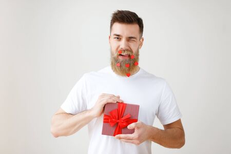 Positive young male has trendy hairdo, long thick beard covered with paper hearts, blinks eye and holds gift box, decorated with red ribbon, flirts with girlfriend, isolated over white background