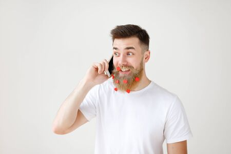 Atrractive smiling bearded male in casual clothes has pleasant talk via smart phone with friend, share news together, has long beard decorated with paper hearts, looks happily aside, isolated on white