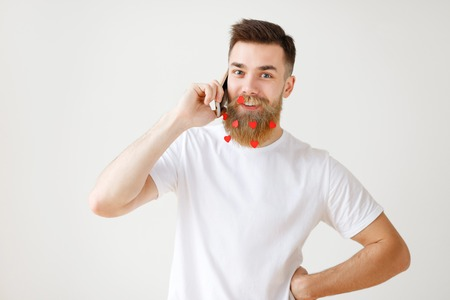 Positive pleasant looking bearded male model with long thick beard being satisfied to have phone conversation and relax after hard working day, enjoys spending time at home, isolated on white wall