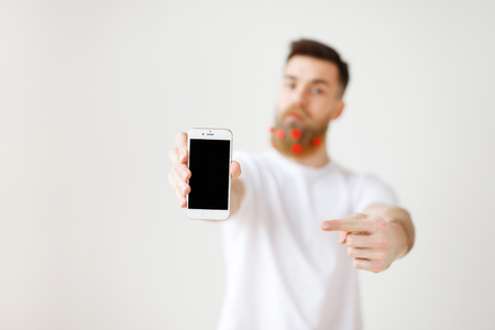 Selective focus. Modern smart phone with blank screen in man s hands. Bearded stylish man advertizes mobile phone in white studio. Up to date electronic device with black screen, isolated on white Stock Photo