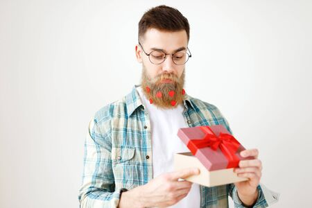 Indoor shot of bearded male model with long thick beard dressed in checkered shirt, opens present box, recieves surprise from girlfriend, isolated over white background. People and celebration Stock Photo