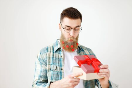 Surprsied handsome man with thick beard and mustache looks with intriguing expression as opens wrapped gift box, being curious what is there, wears round spectacles and checkered shirt, isolated