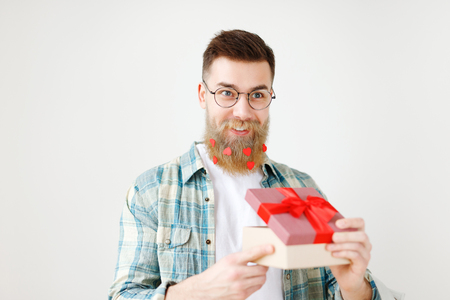 Fashionable bearded hipster guy in eyewear, opens wrapped present, recieves surprise from wife, being in good festive mood, isolated over white background. People, surprisment and presents concept Stock Photo