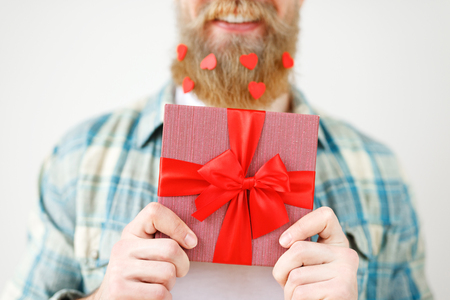 Cropped shot of romantic bearded male holds present box in front, going to make surprise for girlfriend, isolated on white background. Unrecognizable fashionable young guy with wrapped gift box