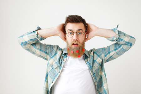 Stupefied surprised man with long beard dressed in fashionable clothes, keeps hand on head, stares through spectacles, being amazed to hear shocking news, isolated over white studio background Stock Photo