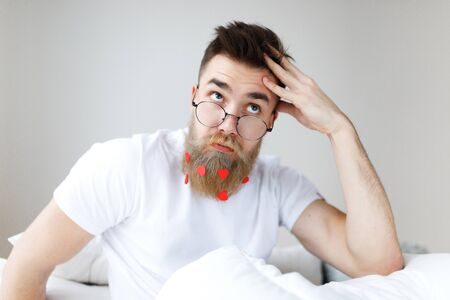 Thoughtful bearded male with trendy hairstyle, mustache and beard, looks pensively upwards through spectacles, plans his working schedule, awakes in morning, finds necessary solution in mind.