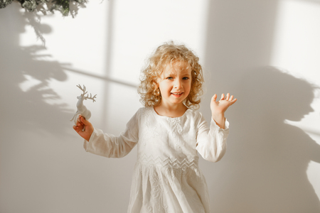 Playful cheerful little beautiful girl with blonde curly hair plays with toy deer, dressed in festive white dress, ready to recieve Christmas presents, isolated over white background with shadow. Stock Photo
