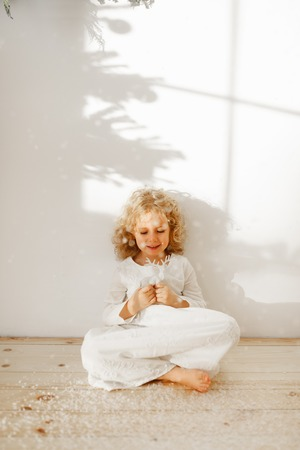 Restful adorable small kid dressed in long white dress, plays with Christmas toy deer, sits crossed legs on wooden floor, isolated over white studio background. Happy child plays with favourite toy.