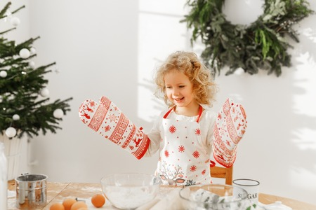 Hard working little child cook wears big kitchen gloves, prepares delicious pastry instead of mother, confident in success, helps parents about house, stands at spacious room decorated with fir tree.