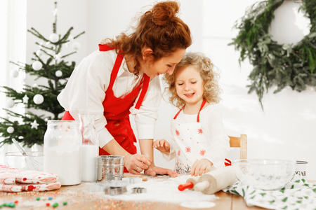Portrait of cheerful mother and daughter wear aprons, stand on kitchen, prepare delicious pie for New Year table. Talented female cook teaches her little child to bake cookies. Parents, baking concept.