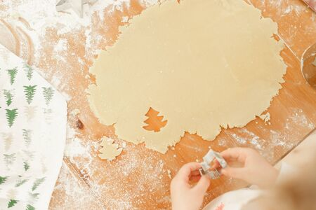 Child s hands make cookies from dough, uses cookie cutter in shape of firtree, prepares for winter holidays, bakes delicious dessert on Christmas, helps parents. Kid cutts out shapes from pastry. Stock Photo