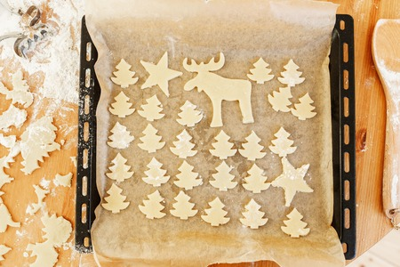 Christmas cookies gingerbread on baking tray. Shapes of deer and firtrees. Delicious sweet biscuit. Top view. Winter holidays, food and celebration concept.