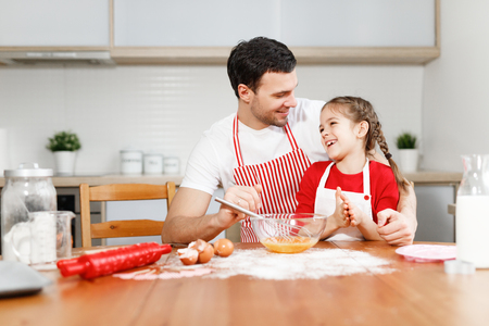 Affectionate brunet young male embraces daughter, sit together at kitchen, bake something delicious, prepare surprise for mother, surrounded with ingredients, mix eggs in bowl. Parenthood concept.
