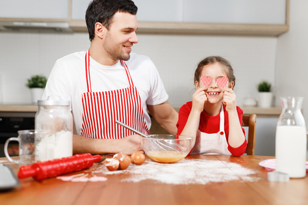 Cheerful brunet male wears apron looks at happy child who covers eyes with hearts, sit at wooden kitchen table, mixe eggs in bowl with whisk, have good time together. Family and childhood concept. Stock Photo