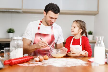 Curious female pretty child helps her father who mixes eggs, sit at kitchen, have pleasant conversation, enjoy togetherness. Little kids and her male parent bakes something delicious for party. Stock Photo