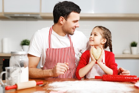 Portrait of handsome affectionate father embraces her little daughter, make cookies together, being in good mood. Domestic atmosphere. Baking concept. Friendly family. Childhood concept.