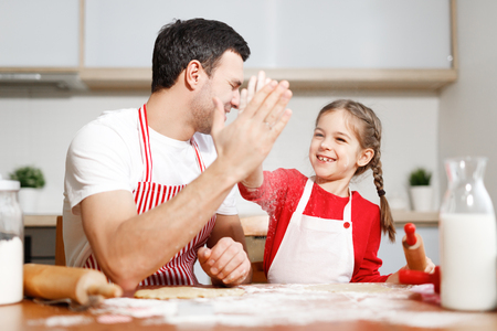 Successful small adorable child and her affectionate father express their agreement between each other, keep hands together, sit at kitchen table, bake delicious apple pie for family on supper.