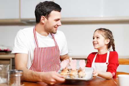 Indoor shot of handsome man wears striped apron and his small pretty female kid hold hand made cakes, rejoices successfully done work on kitchen, being in high spirit, happy spend time together.